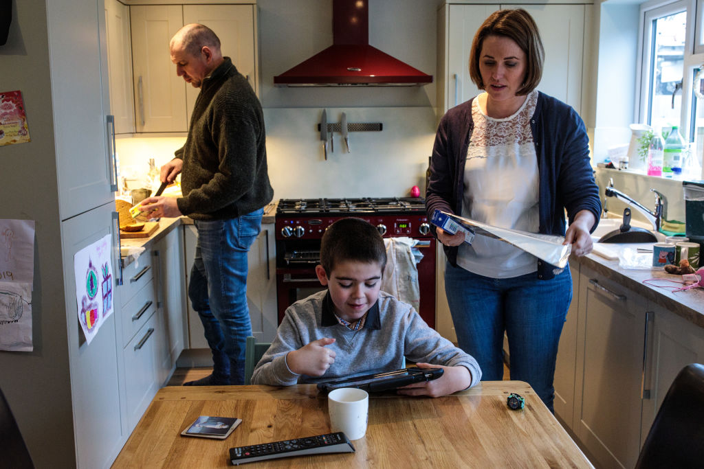 Alfie Dingley watches a video on a tablet as his parents Drew Dingley and Hannah Deacon prepare lunch at their home