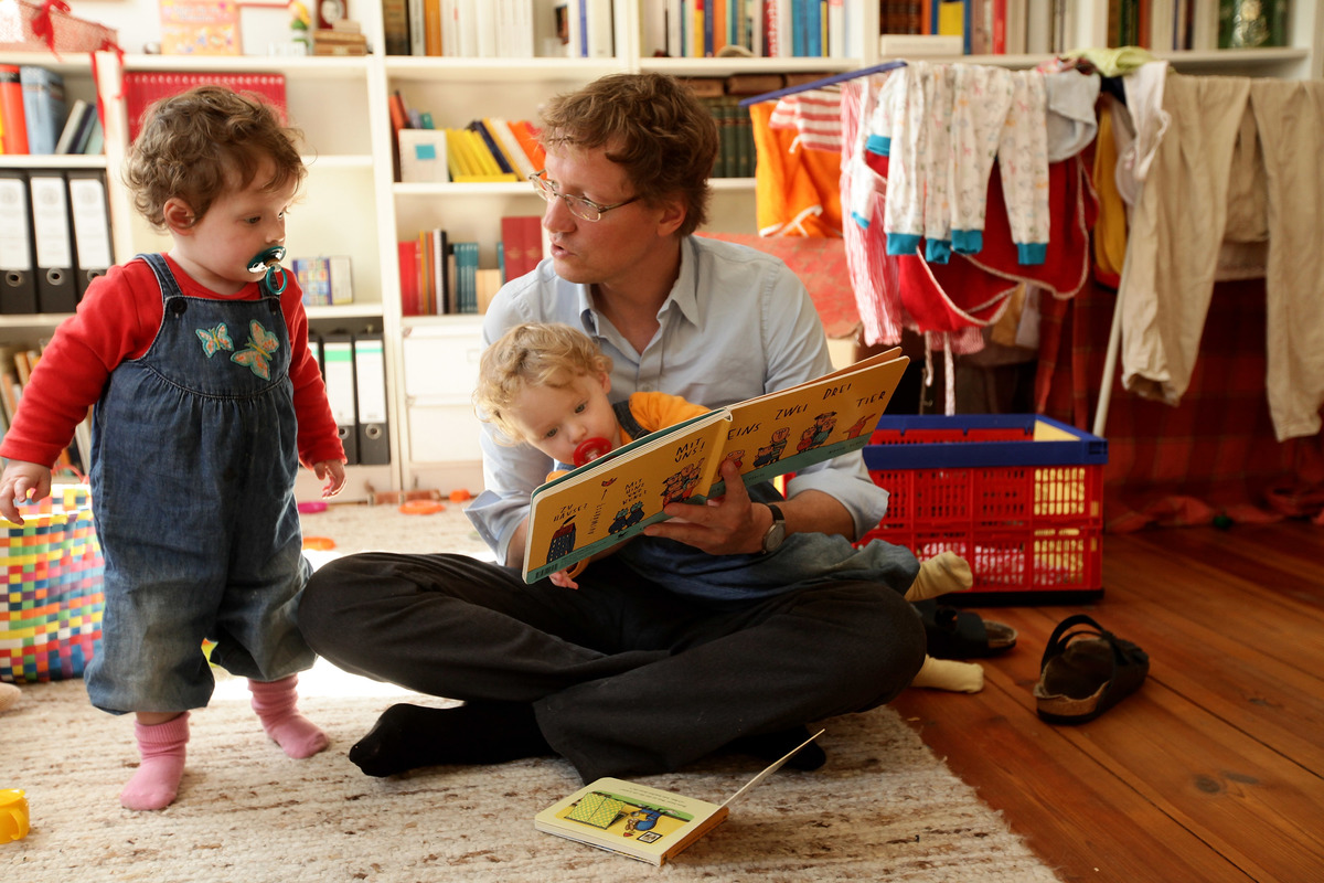 dad reading with 14-month old twin girls in Berlin