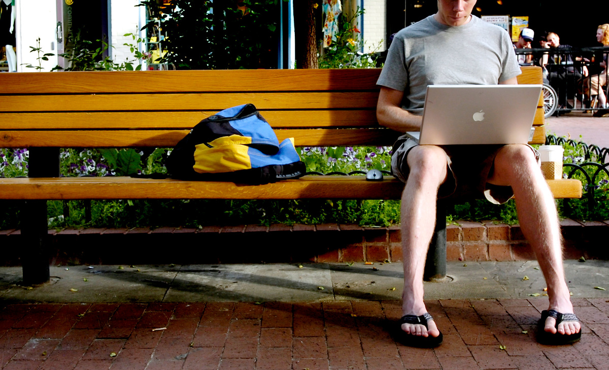 a man works on his computer on a bench