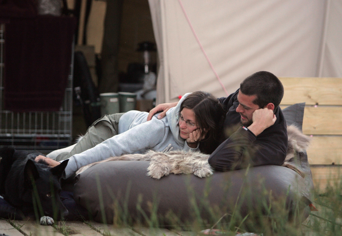 couple with dog on ground outside a tent
