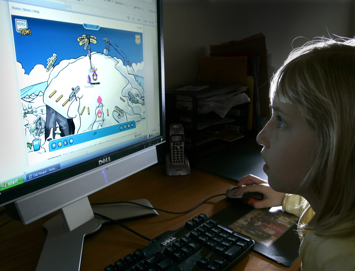 girl playing club penguin on computer in 2008