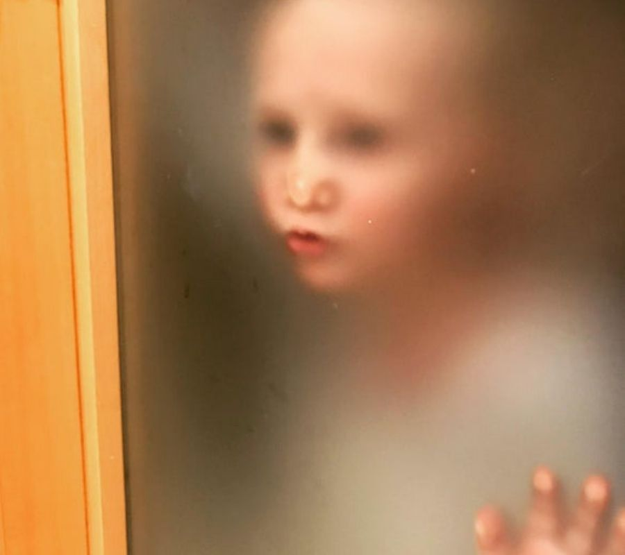 creepy toddler on door mouth pressed against nasty