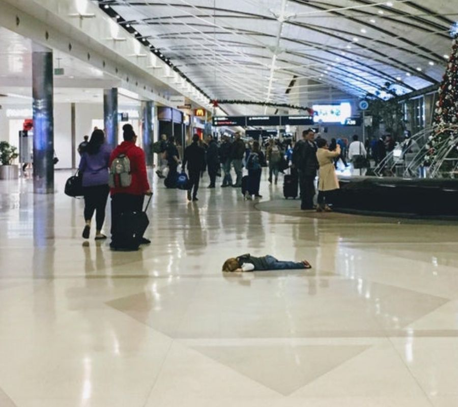 toddler laying down on the ground at the airport looking like a dang fool