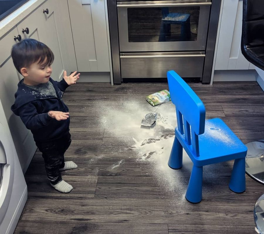kid standing in front of chair flour all over the floor mess