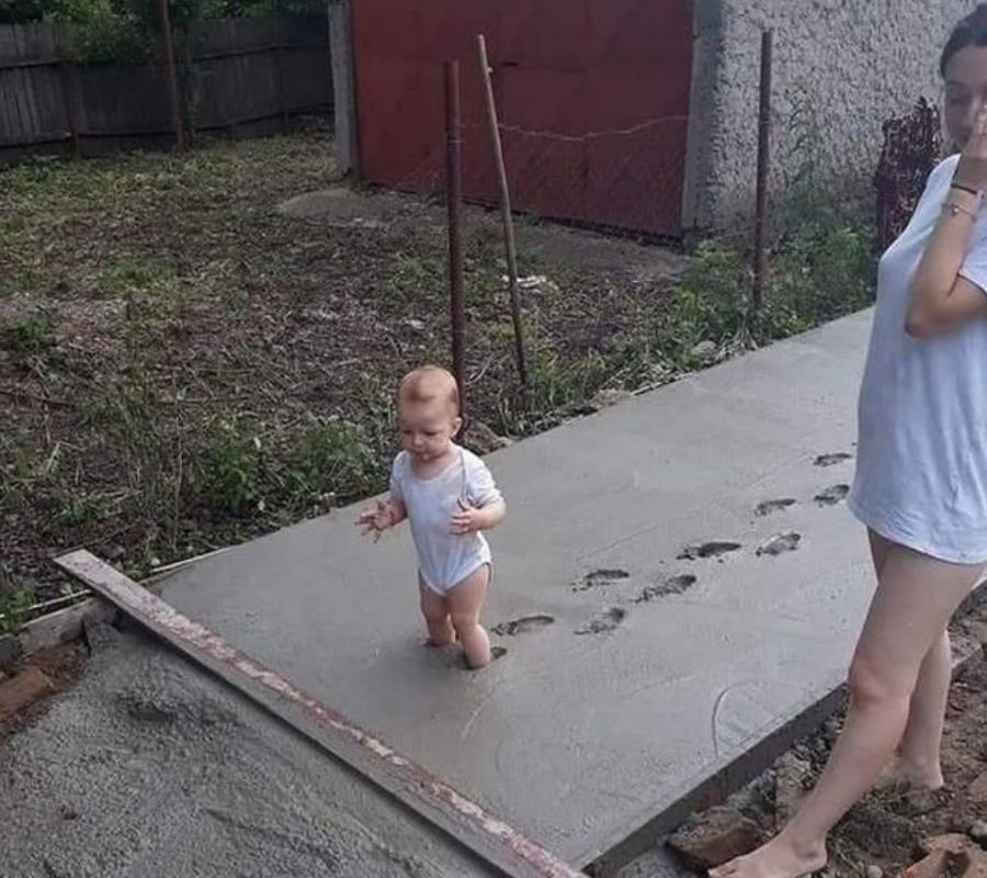 baby in concrete walking through mom looking stressed