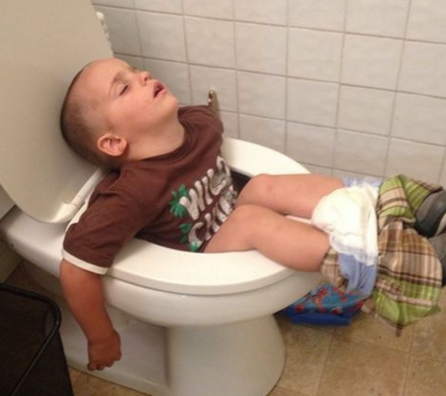 kid sleeping on the toilet completely inside of it