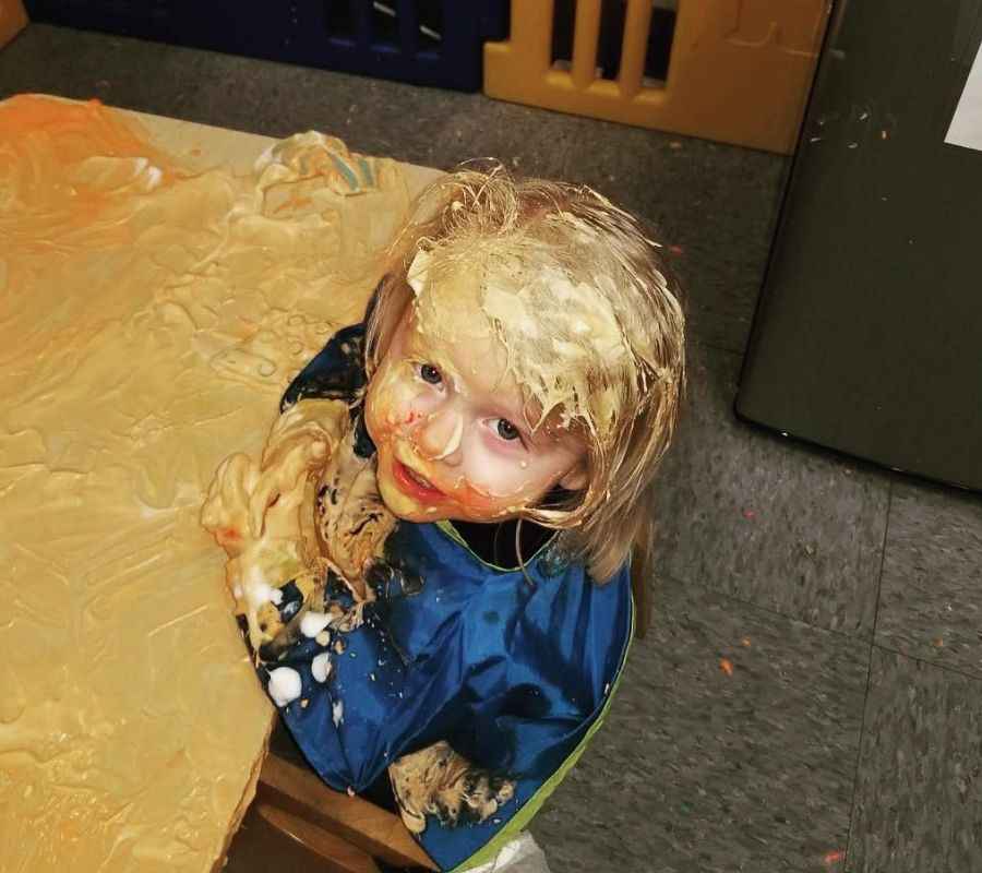 kid covered in beige paint at daycare looking at camera