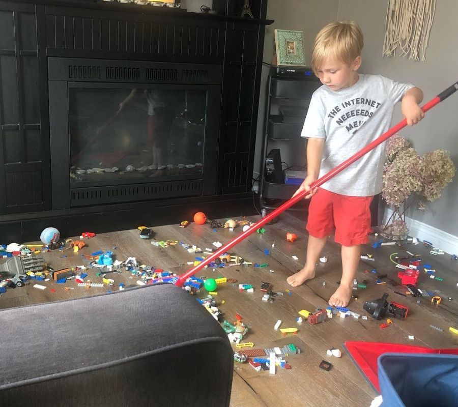 kid cleaning up legos on the floor