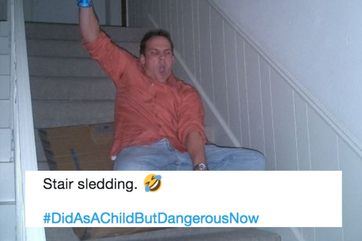 riding down a staircase on cardboard in salmon shirt