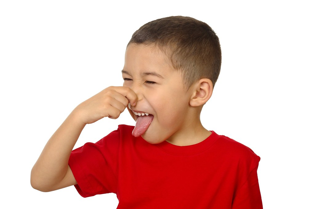 kid plugging nose stock photo