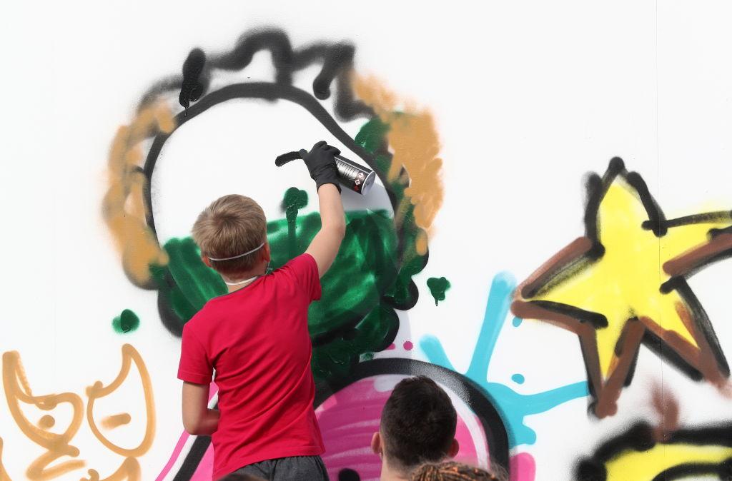 a boy spray paints a wall
