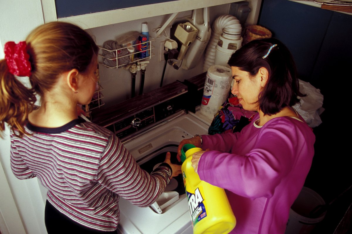young child helping parent do laundry