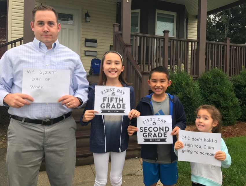 entire family holding back to school signs