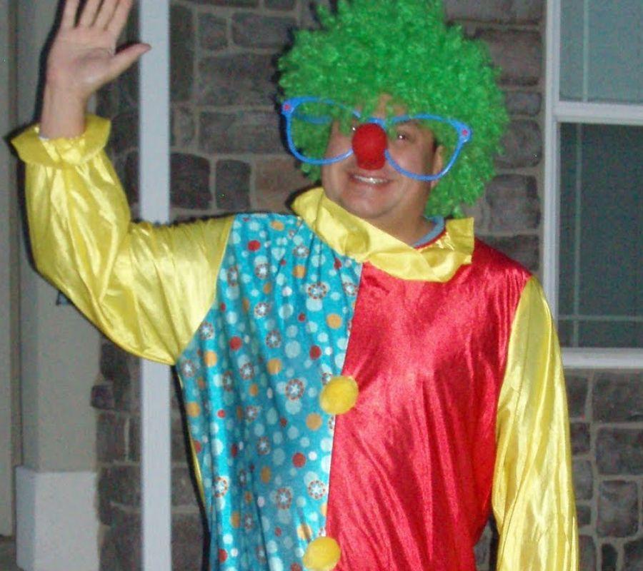man waving in clown costume