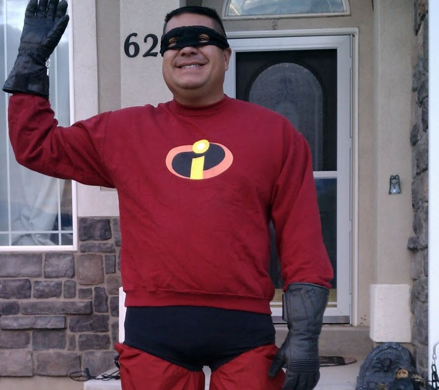 man in incredibles outfit waving