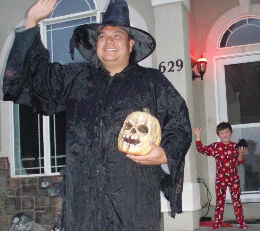 father dressed in witch costume waving