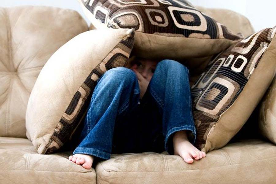 a boy hides in some pillows