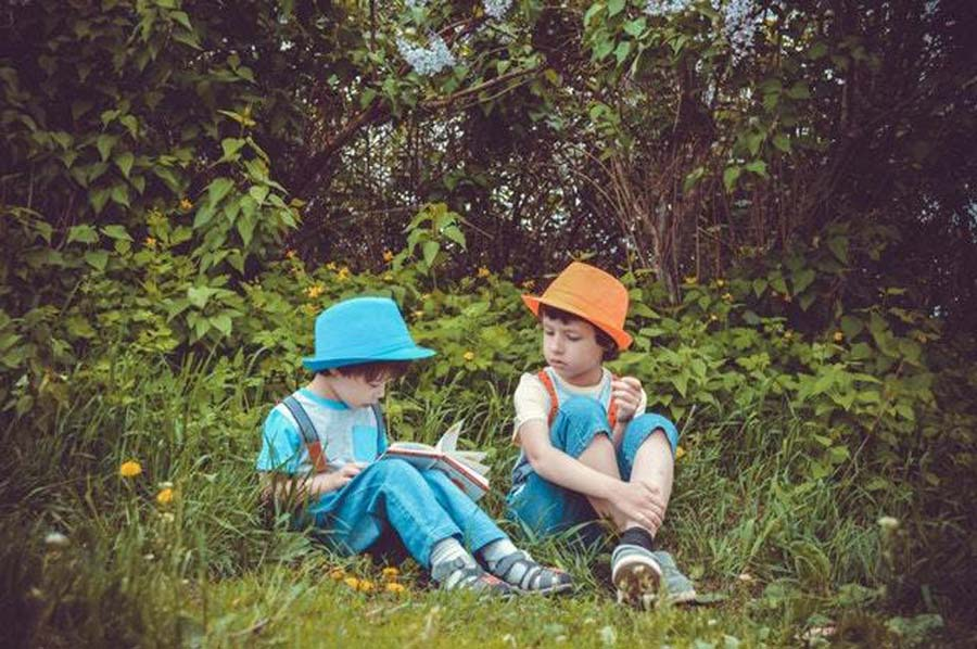 two boys sitting outside