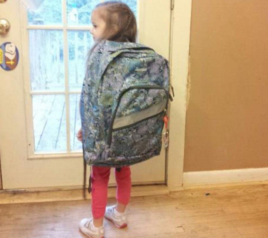 girl wearing giant bag back to school