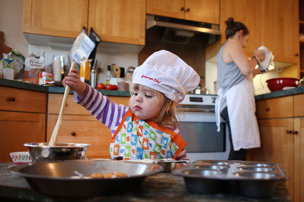 A two year old girl cooking with her mom in the kitchen