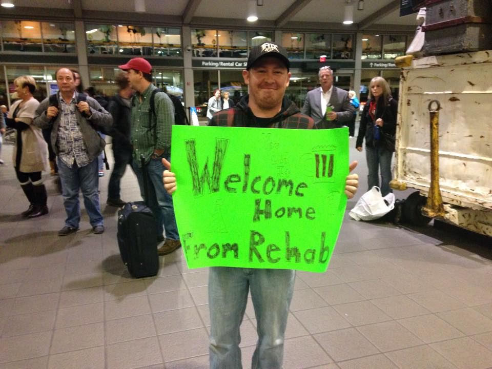 brother holding 'welcome home from rehab' sign for sister who is not coming home from rehab