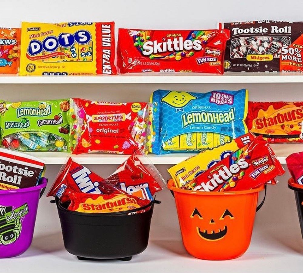 Packages of candy on shelves and in buckets