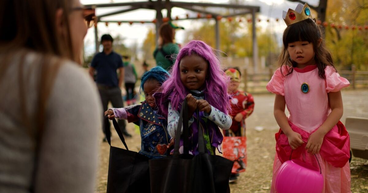 hildren dressed in halloween costumes asks trick-or-treat t