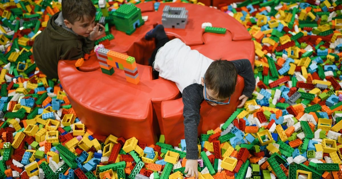 Two children play in a large exhibit of Lego pieces