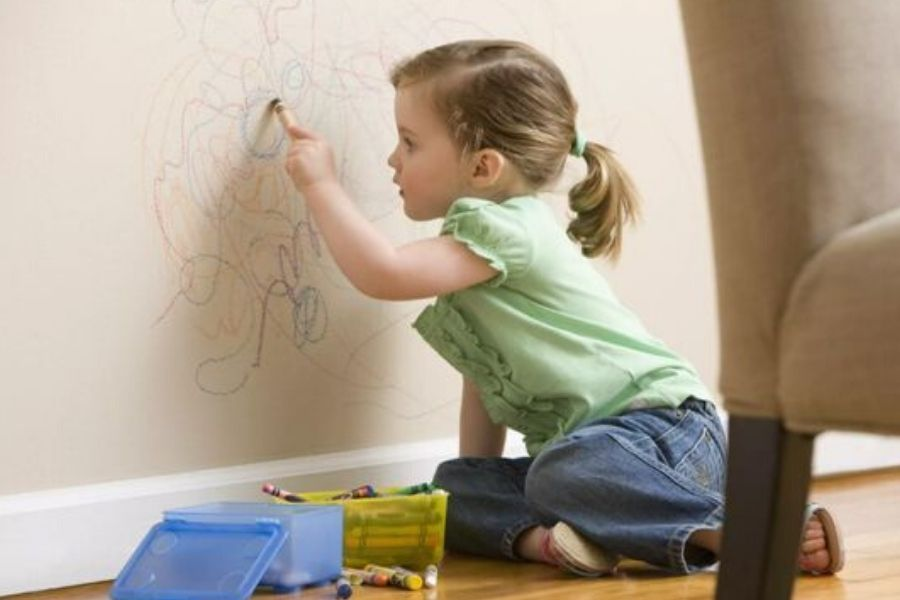 girl doodling on wall with crayon