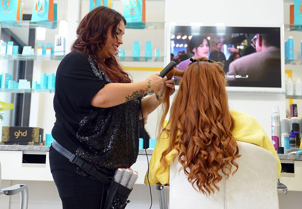 Woman getting hair straightened