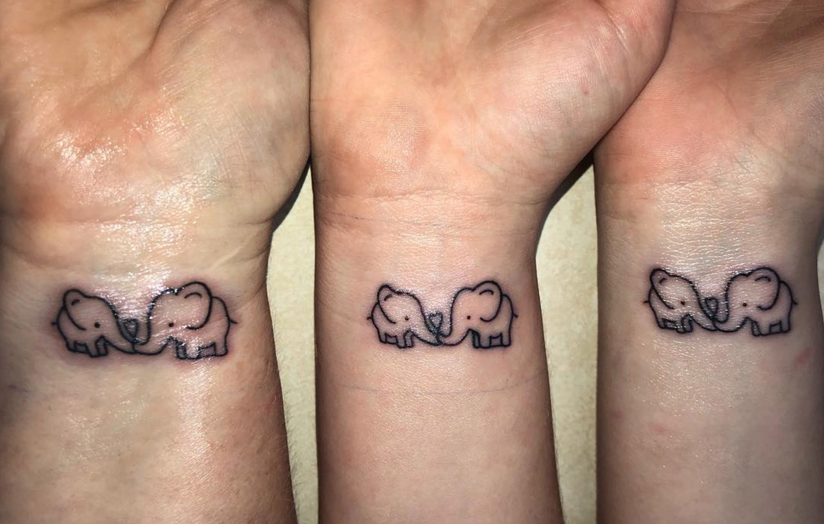 mother and two daughters with matching tattoos of elephants touching trunks