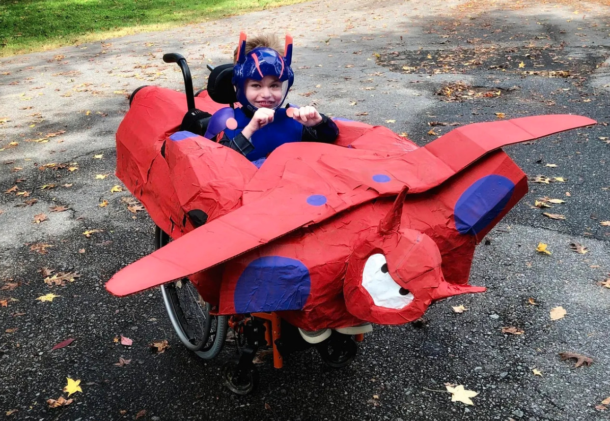 photo of child in wheelchair shaped like a plane