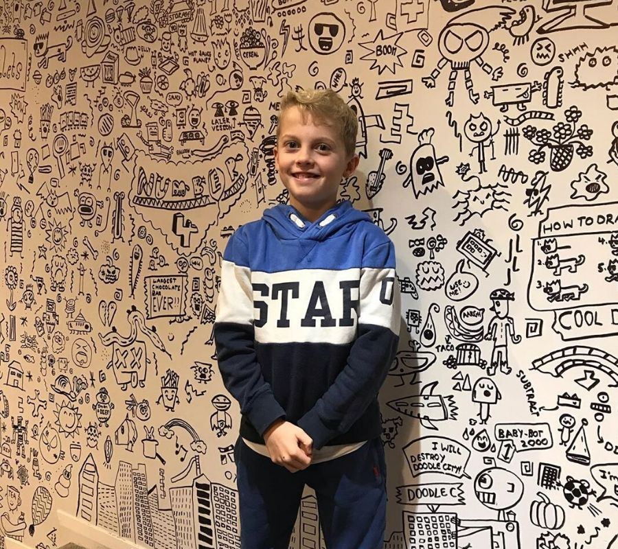 kid standing in front of a wall