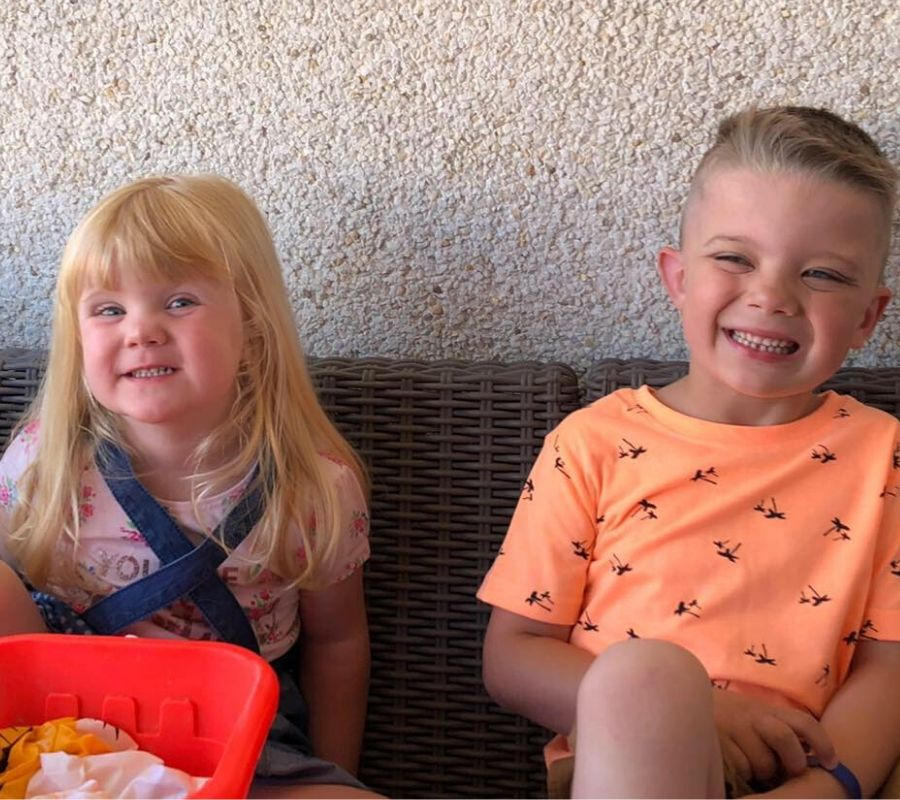 two kids sitting and smiling