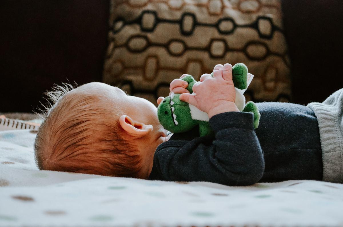 baby cuddling little stuffed animal
