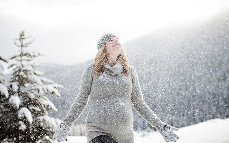 pregnant woman in snow without a coat
