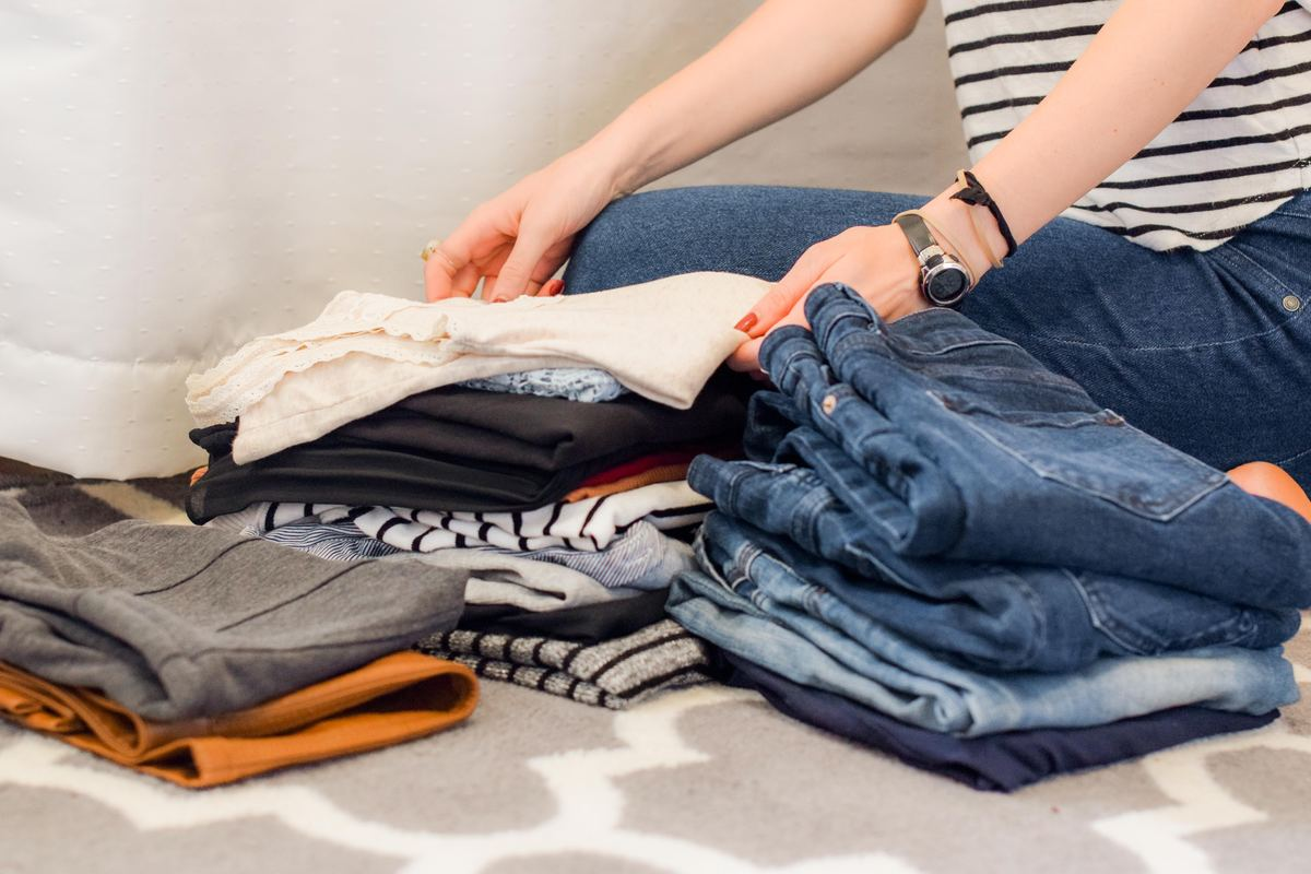 woman folding a pile of clothing