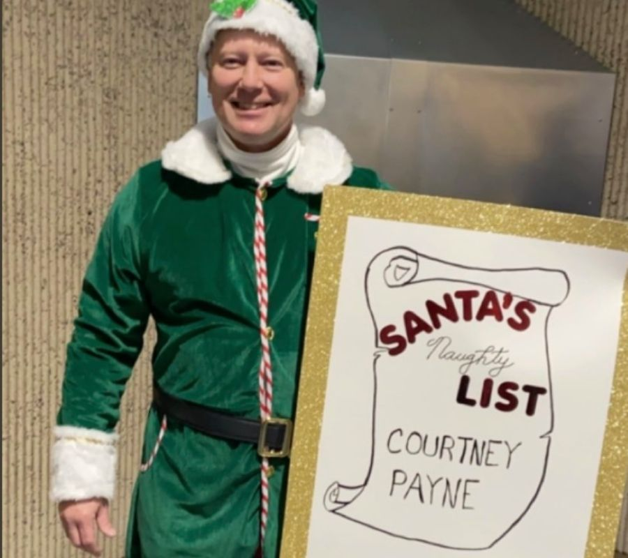 dad dressed up as an elf holding a sign that says,
