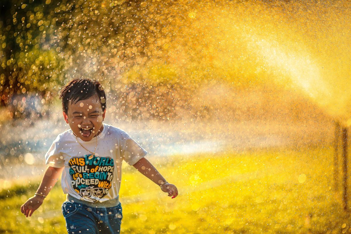kid running through sprinkler spray