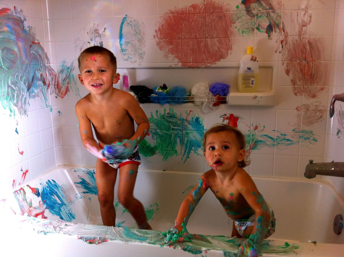 kids fingerpainting in bathtub using colored shaving cream