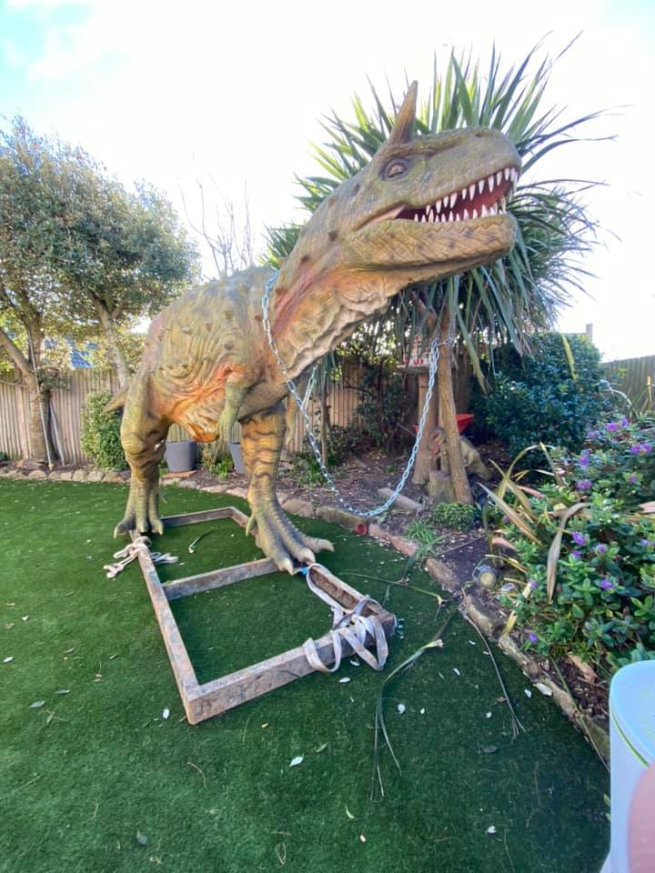 dinosaur statue place in andre's yard