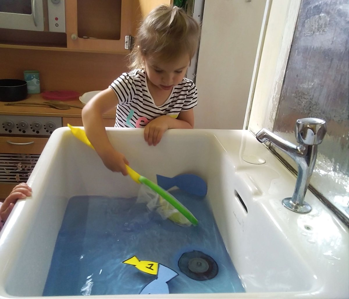 small child fishing in the sink
