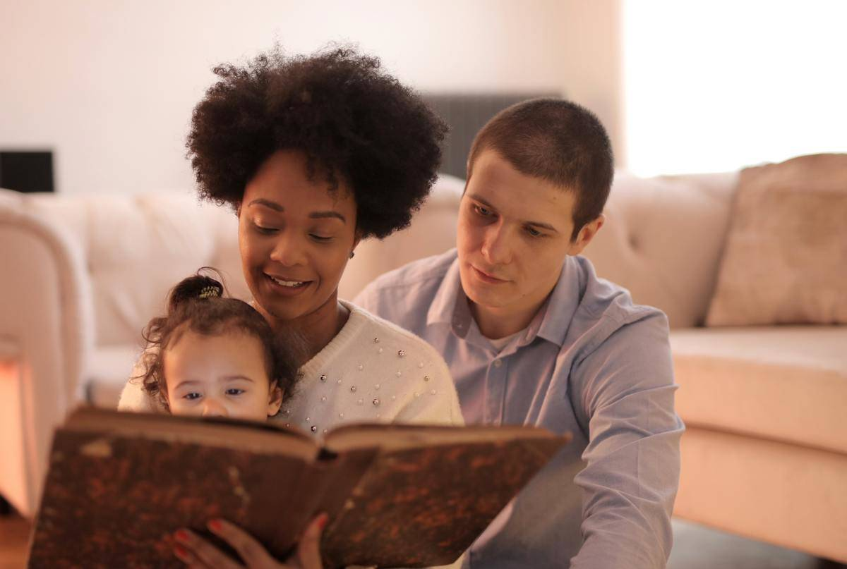 family reading book with children