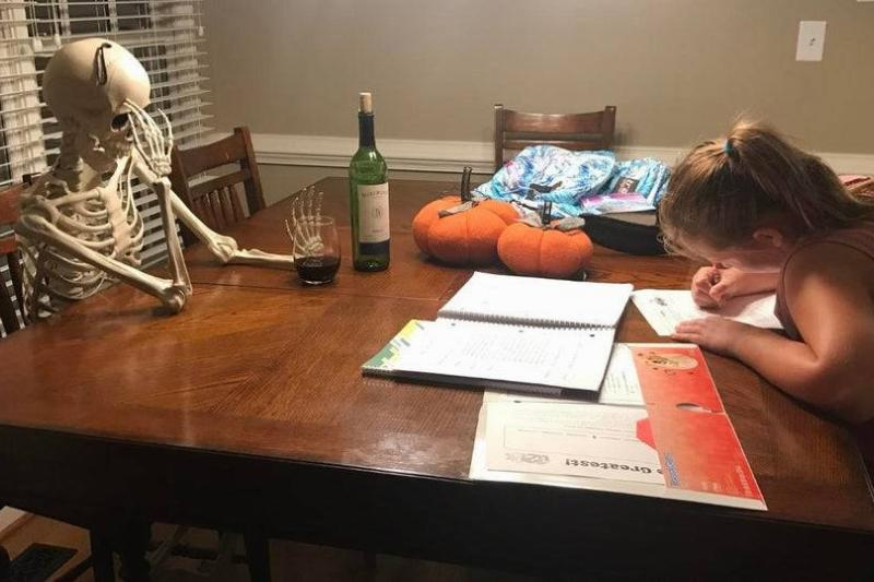 a little girl sitting with a skeleton doing homework