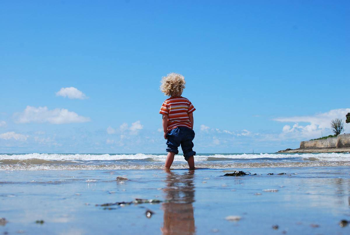 little boy on beach standing at edge of water