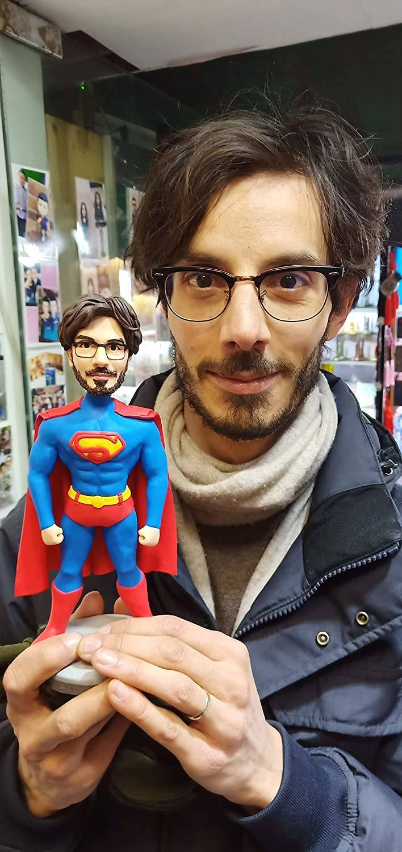 man holding custom bobblehead of himself as superman
