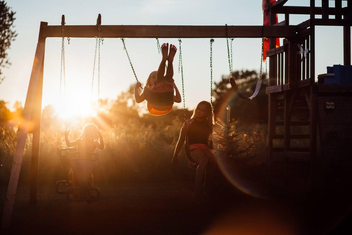three children on swings at sunset