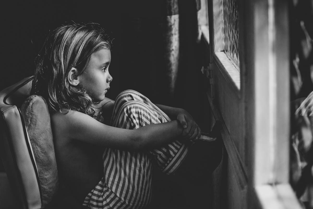 Grayscale photography of child sitting front of window