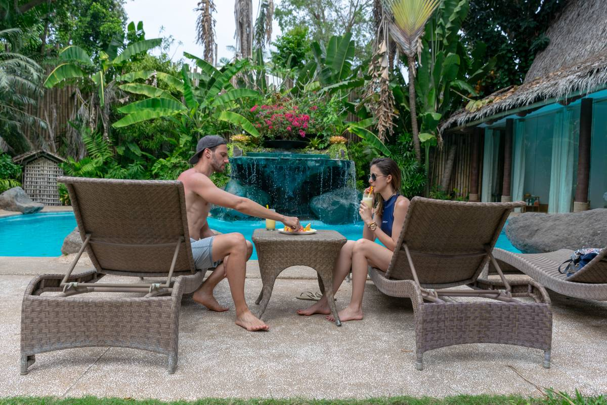 Man and woman sitting on brown lounge chairs