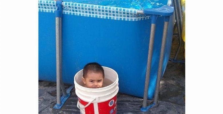 kid sitting in bucket